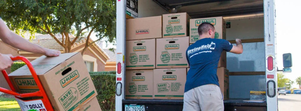 Image: an Emerald Coast Moving crew member packing a moving truck with boxes.